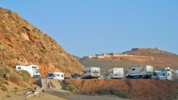 Mehrere Wohnmobile stehen auf einem Parkplatz, im Hintergrund felsige Hügel