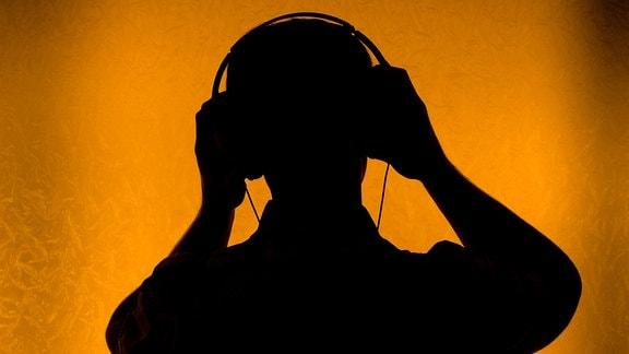 Silhouette eines Menschen mit Kopfhörern.