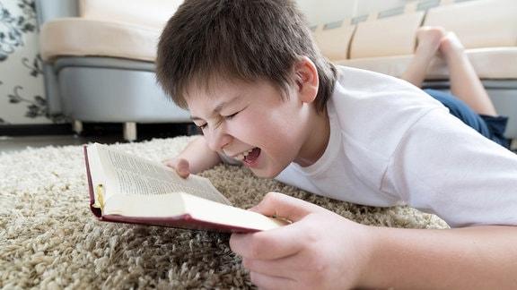 Ein lachender Junge liegt mit einem Buch auf dem Wohnzimmerboden