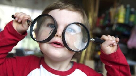 Ein kleiner Junge sieht durch zwei Lupen
