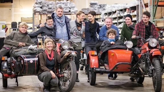 Menschen posieren mit Motorrädern für ein Gruppenfoto