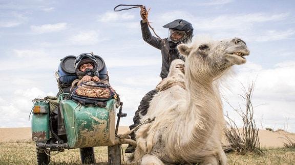 Menschen mit Motorrad und Kamel