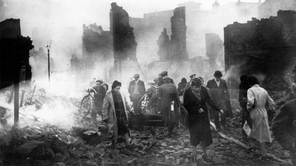 Menschen bewegen sich nach einer Bombardierung im November 1940 durch Gebäudeüberreste in der englischen Stadt Coventry.
