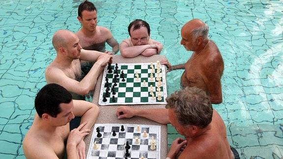 Männer spielen im Aussenbecken eines Thermalbades Schach