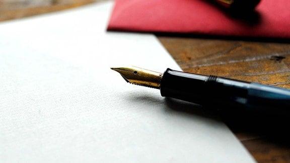Ein Füllfederhalter liegt auf einem Blatt Papier.