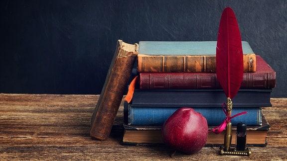 Bücher gestapelt, ein Apfel und eine Feder davor