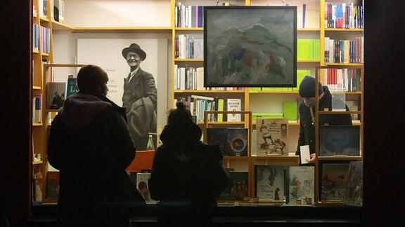 Zwei Menschen sehen sich die Schaufenster-Auslage der Buchhandlung Jacobi und Müller in Halle an. Drinnen ist eine Person mit Gesichtsmaske.