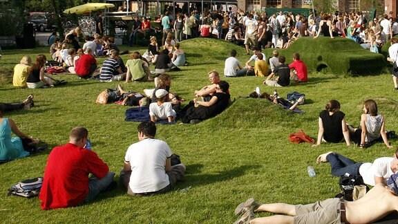 Menschen liegen und sitzen in einem Park