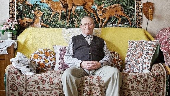 Ein älterer Herr sitzt auf seiner Couch im Wohnzimmer und lächelt in die Kamera.