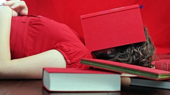 Ein Mädchen hat ihr Gesicht liegend unter einem Buch vergraben.