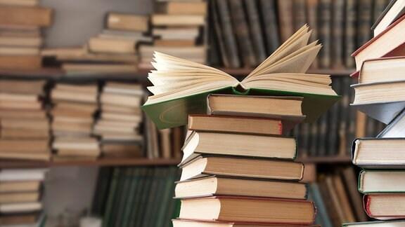 Bücherstapel vor einem Bücherregal