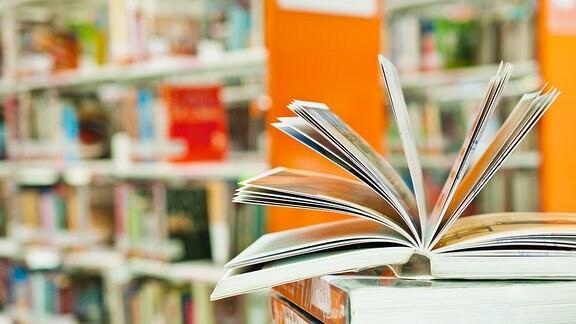 Bücher liegen auf einem Stapel vor einem Bücherregal.