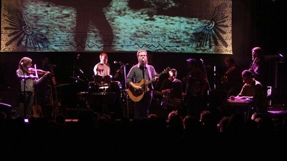 Calexico und Iron & Wine während eines Konzertes auf der Bühne.