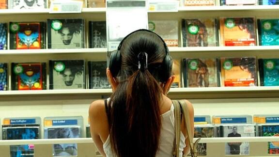 CD des Jahres - Ein eFrau mit Kopfhörern vor einem Regal mit Cds.