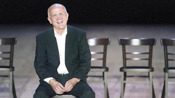 Der Schauspieler Christian Grashof sitzt auf einem Stuhl und lacht.