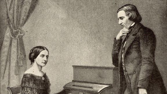 Robert Schuhmann steht neben einem Klavier, an dem seine Frau Clara Schuhmann spielt.