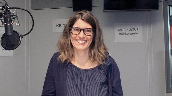 Claudia Tittel. Eine junge Frau mit Brille und langen Haaren steht im Studio neben einem Mikrofon und schaut lächelnd in die Kamera.