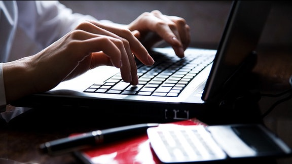 Eine Frau schreibt auf einer Laptop-Tastatur.