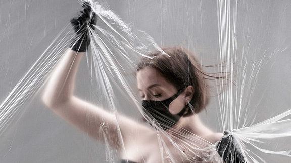 Eine halbnackte Frau mit Mundschutz steht hinter einer Folie