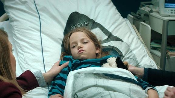 Ein Kind liegt im Krankenbett, rechts und links davon Mutter und Vater.