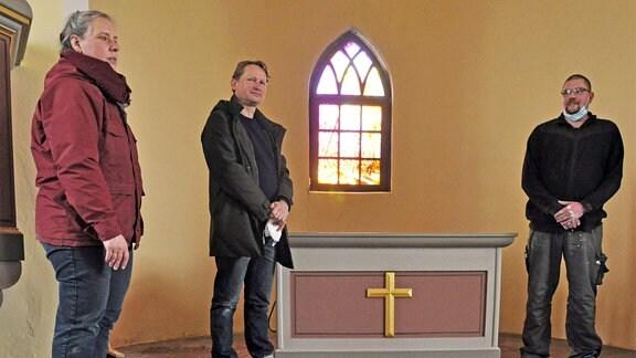 Drei Personen stehen in einer Kirche vor dem Altar, im Hintergrund ein Kirchenfenster.