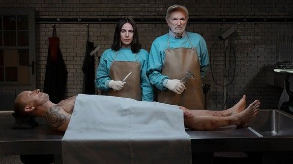 """""""Dead End"""" (Key Visual): Emma (Antje Traue) und ihr Vater Peter (Michael Gwisdek) stehen mit Obduktionsbesteck vor einem Seziertisch. Vor ihnen liegt ein Toter, den sie untersuchen müssen."""
