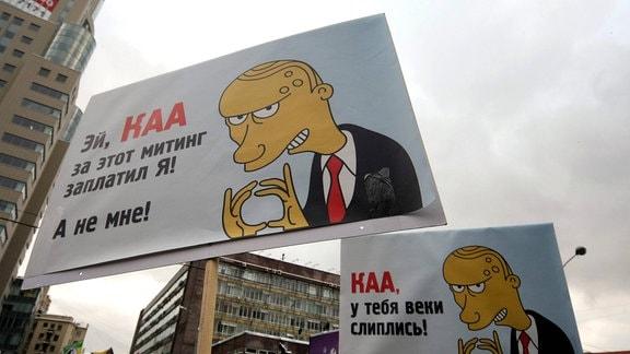 Banner mit Karikaturen von Putin während eines Protestes der Opposition im Sacharow-Prospekt im Zentrum Moskaus.