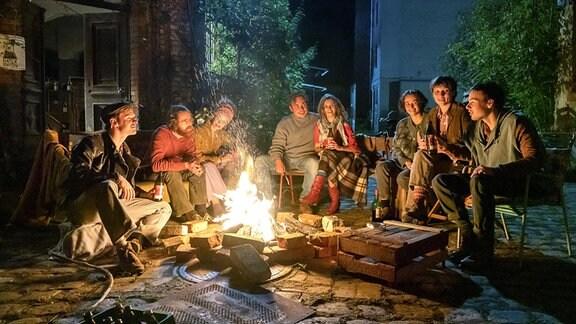 Menschen sitzen um ein Feuer