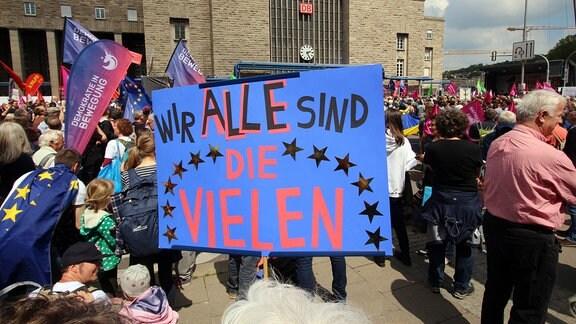 """Demonstranten halten Plakat mit der Aufschrift """"Wir alle sind die Vielen"""""""