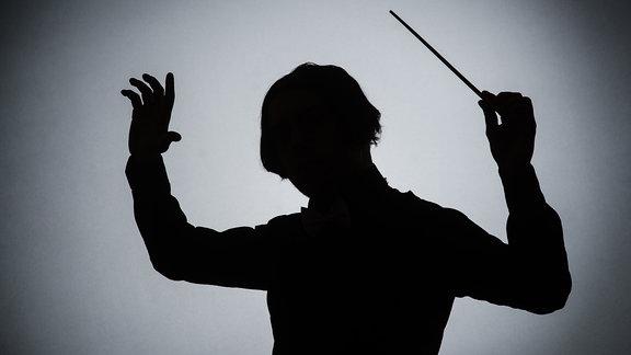 Silhouette eines Dirigenten mit Taktstock
