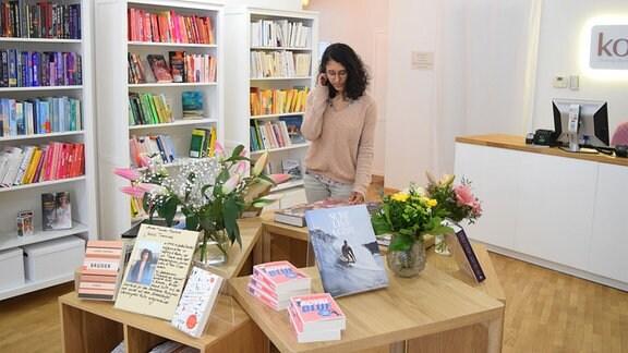 Eine Frau steht an Buchauslage in der Diversity-Buchhandlung kohsie in Halle.