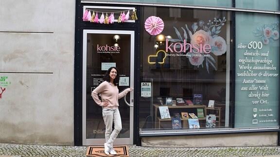 Eine Frau steht vor der Diversity-Buchhandlung kohsie in Halle und schaut lächelnd in die Kamera.