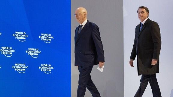 Prof. Klaus Schwab und Brasiliens Präsident Jair Bolsonaro betreten die Bühne beim Weltwirtschaftsforum in Davos 2019.