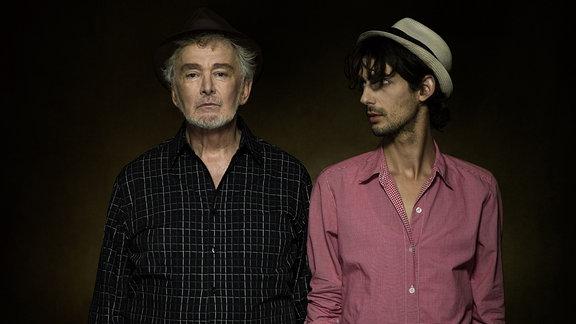 Senior neben einem jugen Mann mit Hut