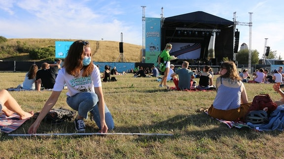 Menschen sitzen auf einer Wiese vor einer Bühne.