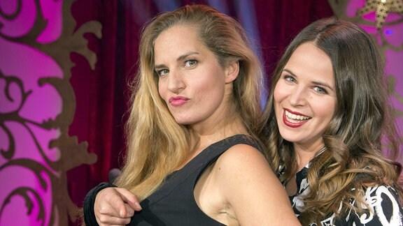Zwei Frauen auf Bühne schauen lächelnd in die Kamera.