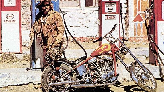 Filmszene: Dennis Hopper mit Maschine an der Tankstelle