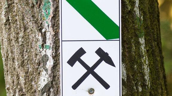 Wanderzeichen und Symbol Schlägel und Eisen für Bergbaupfad an einem Baum