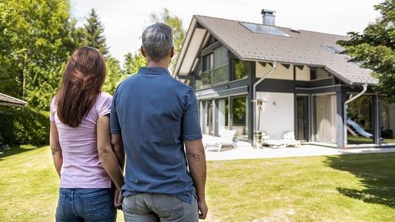 Frau und Mann stehen Hand in Hand vor einem Haus.
