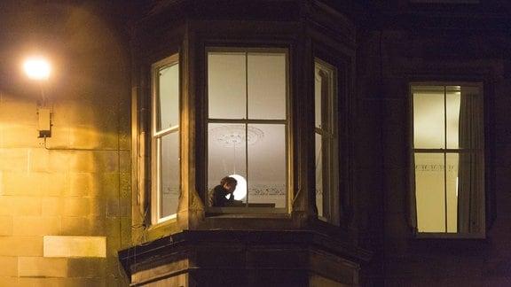 einsamer Student lernt nachts an einem beleuchteten Fenster in Edinburgh