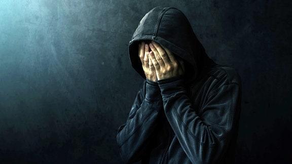 Ein Mann mit Kapuzenpullover hät sich die Hände vor das Gesicht