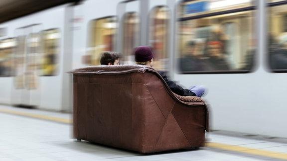 Fahrgäste sitzen auf einer Couch in der Haltestelle Appellhofplatz.