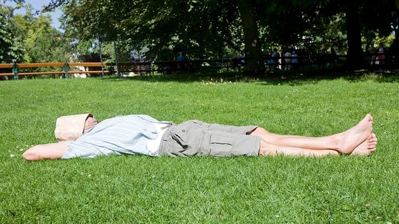 Ein  Mann liegt auf einer Wiese und ruht. Über sein Gesicht hat er als Sonnenschutz einen faltbaren Stadtplan gelegt.