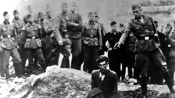 Ein Soldat der Einsatzgruppe D ist im Begriff, 1942 einen Juden zu erschießen, der an einem teilweise gefüllten Massengrab in Vinnitsa, Ukrainische SSR, Sowjetunion, niederkniet.