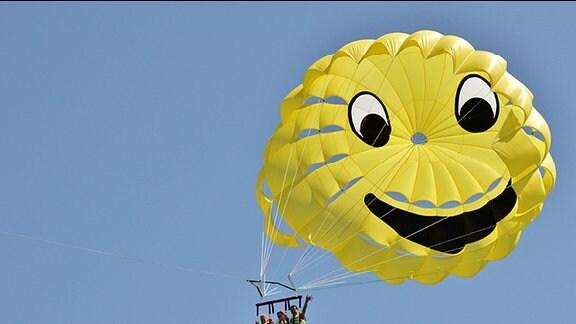 Drei Personen hängen an einem gelben Fallschirm.