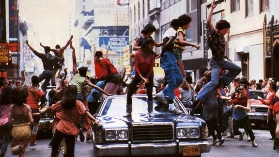 """Junge Menschen tanzen auf einem Auto auf der Straße - Filmausschnit aus """"Fame - Der Weg zum Ruhm"""" (1980)."""