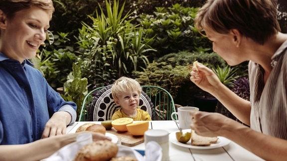 Zwei Frauen und ein Kind am Frühstückstisch