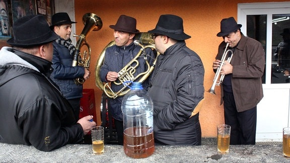Mitglieder der Band Fanfare Ciocarlia vor der Bar in ihrem Dorf Zece Prăjini (Rumänien, Region Moldova)
