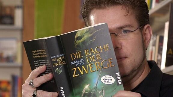 """Fantasy-Autor Markus Heitz mit einer Ausgabe seines Romans """"Die Rache der Zwerge"""""""