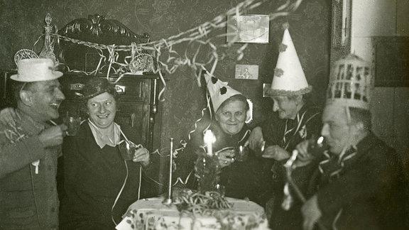 Aufnahme ca. 1948, Menschen sitzen bei einer Feier zusammen.